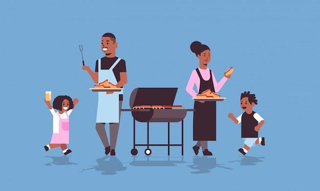 Familie bereitet hot dogs auf grill afroamerikaner eltern und kinder vor, die spaß picknick barbecue party konzept flach in voller länge horizontal haben