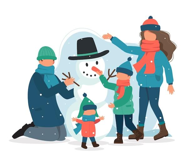 Familie, die einen schneemann im winter macht.