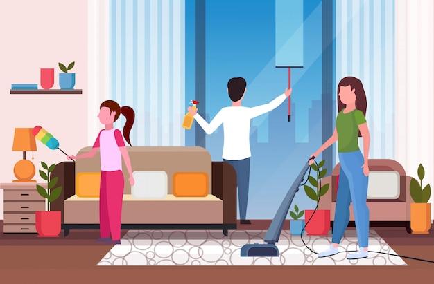 Familie, die hausarbeit zusammen macht vater, der glasfenstermutter abwischt, die staubsauger-tochter staubt, die reinigungskonzeption des modernen wohnzimmerinnenraums in voller länge horizontal wäscht