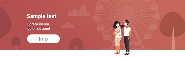 Familie in gesichtsmasken zu fuß im freien giftige luftverschmutzung industrie smog verschmutzte umwelt konzept eltern und kind zusammen stehen riesenrad hintergrund in voller länge horizontale kopie raum