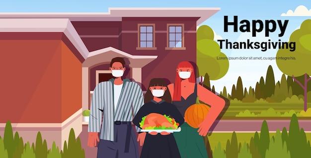 Familie in masken feiern glücklichen erntedankfest eltern und kind in der nähe von haus coronavirus quarantäne konzept porträt stehen