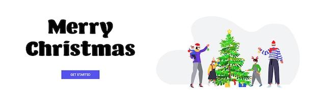 Familie in weihnachtsmützen, die weihnachtsbaumeltern mit kindern verzieren, die masken tragen, um horizontales banner des neujahrsfeiertagskonzeptes der coronavirus-pandemie zu verhindern