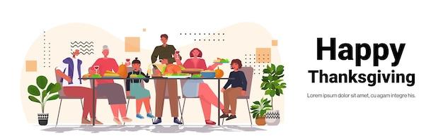 Familie mit mehreren generationen, die glückliche erntedankfest-leute feiern, die am tisch sitzen und traditionelles abendessen haben