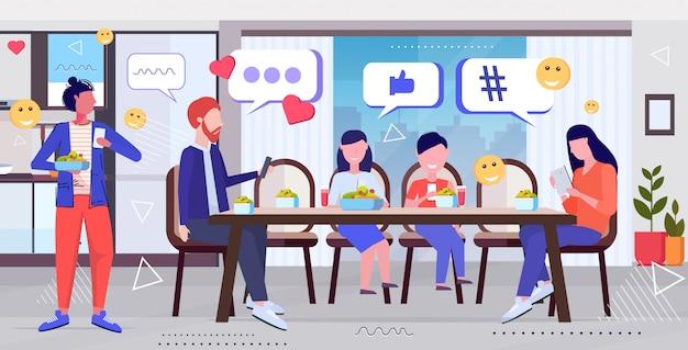 Familie mit online-mobile-app social-media-netzwerk chat blase kommunikation digitale sucht konzept menschen sitzen am esstisch moderne küche innenskizze in voller länge horizontal