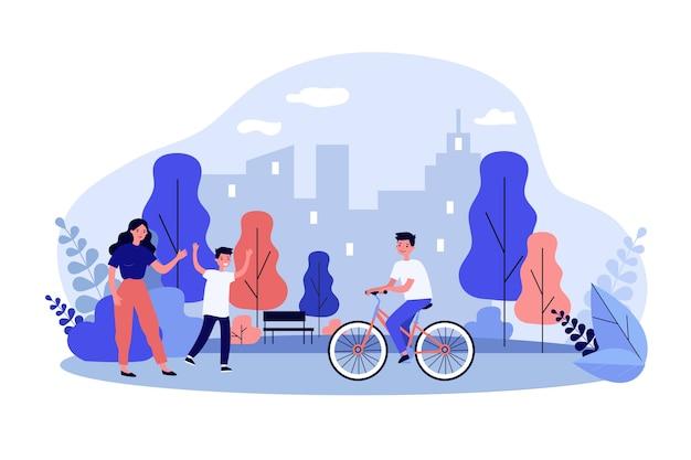 Familie winkt dem jungen, der auf fahrrad im park reitet