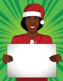 Farbige pop-art-stilillustration. geschäftsfrau, die ein leeres plakat hält. afroamerikanische frau, die einen weihnachtsmannhut auf ihrem kopf mit einem weißen laken in ihren händen trägt. büropartyfeier.