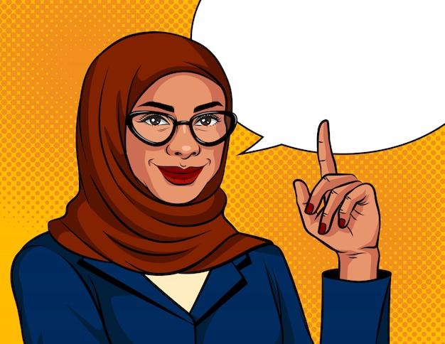 Farbillustration im pop-art-stil. die muslimische frau in einem traditionellen schal und einer brille zeigt mit dem finger nach oben. werbebanner mit arabischer erfolgreicher geschäftsfrau über punkthintergrund