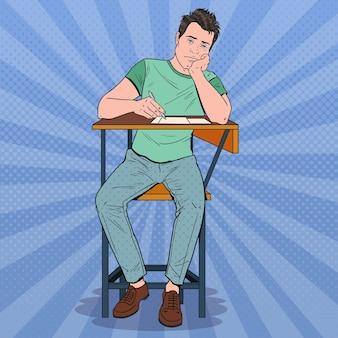 Fauler student der pop-art, der während des langweiligen universitätsvortrags auf dem schreibtisch sitzt. müder hübscher mann im college. bildungskonzept.
