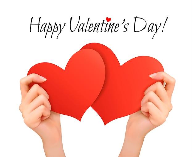 Feiertags-valentinstaghintergrund mit den händen, die zwei rote herzen halten.