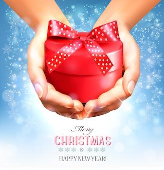 Feiertagsweihnachtshintergrund mit den händen, die geschenkbox halten. konzept des schenkens.