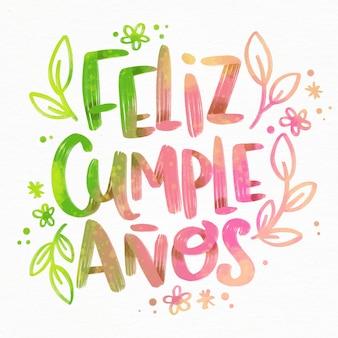 Feliz cumpleaños schriftzug mit blumen und blättern