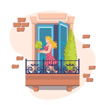Fenster mit jungem mädchen auf balkon kümmert sich um pflanzen. außenansicht der hausfassade mit balkon und dekorationen. außenterrasse auf backsteinbau in stadt oder gemeinde.