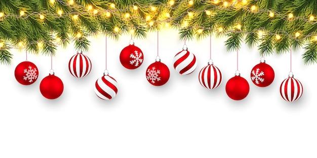 Festlicher weihnachts- oder neujahrshintergrund. weihnachtstannenzweige mit heller girlande und weihnachtlichen roten kugeln. urlaub hintergrund.