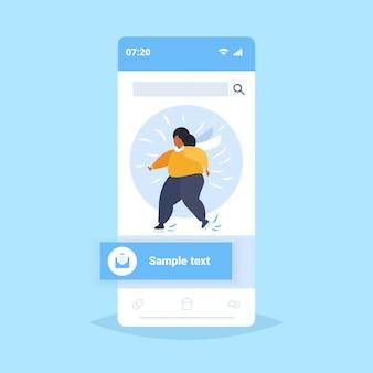 Fett fettleibige frau schlittschuh auf eisbahn übergewichtige afroamerikanerin, die aktive freizeit in der wintersaison gewichtsverlust konzept smartphone bildschirm online-mobile-app durchführen