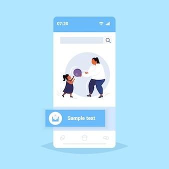 Fett fettleibige mutter mit tochter spielt mit ball übergewichtige frau und kind, die spaß zusammen gewichtsverlust körperliche aktivität konzept smartphone-bildschirm online-mobile-app in voller länge haben