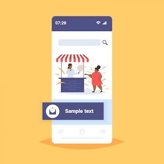 Fett fettleibiges mädchen kaufen eis am lebensmittelstand ungesunde ernährung fettleibigkeit konzept weibliches afroamerikaner-kind, das spaß smartphone-bildschirm online-mobilanwendung hat