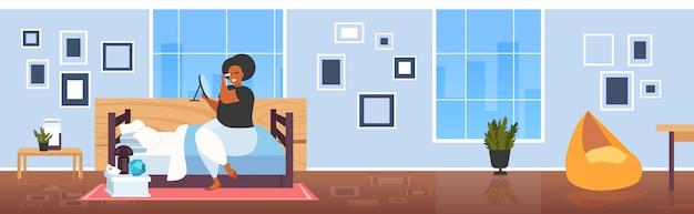 Fette fettleibige frau, die schwarze wimperntusche afroamerikanisches mädchen anwendet, das spiegel berührt, das wimpern unter verwendung der quaste berührt, die professionelles modernes schlafzimmerinnenraum in voller länge horizontal bildet