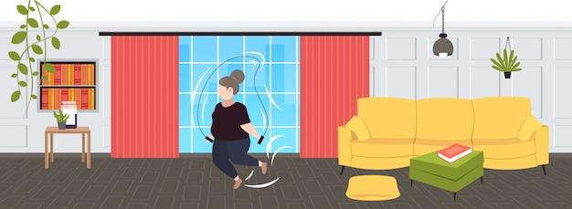 Fette fettleibige frau, die übungen mit springseil übergewichtiges mädchen cardio-training workout gewichtsverlust konzept modernes wohnzimmer interieur in voller länge horizontal macht
