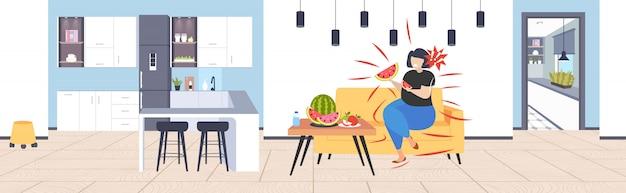 Fette fettleibige frau, die wassermelone und apfel frisches obst diät afroamerikanermädchen gesunde ernährung gewichtsverlust konzept moderne küche innen horizontale volle länge isst