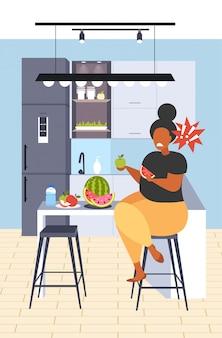Fette fettleibige frau, die wassermelone und apfel frisches obst diät afroamerikanermädchen gesunde ernährung gewichtsverlust konzept moderne küche interieur vertikale volle länge isst