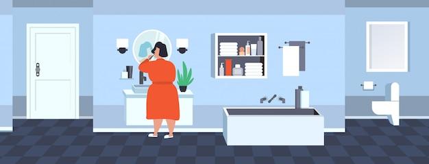 Fette fettleibige frau, die zähne übergewichtiges übergewichtiges afroamerikanisches mädchen hält, das zahnbürste hält, die spiegelübergewichtkonzept des modernen badezimmerinnenraums in voller länge rückansicht horizontal betrachtet