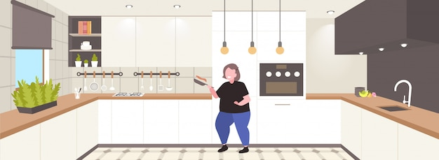Fette fettleibige frau kocht pfannkuchen in der pfanne ungesunde ernährung fettleibigkeit konzept übergewichtiges mädchen, das frühstück modernes kücheninterieur vorbereitet