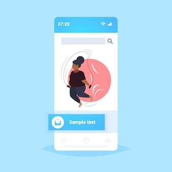 Fette fettleibige frau macht übungen mit springseil übergewicht afroamerikaner mädchen cardio training workout gewichtsverlust konzept smartphone bildschirm online-mobile-app in voller länge