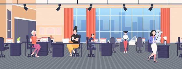 Fette fettleibige geschäftsfrau, die schokolade übergewichtiges mädchen isst, das am arbeitsplatz schreibtisch mit laptop ungesunde ernährung fettleibigkeit konzept modernen arbeitsbereich büro interieur in voller länge horizontal sitzt