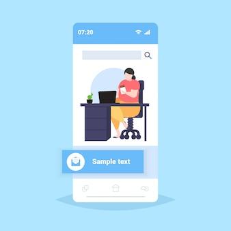 Fette fettleibige geschäftsfrau, die übergewichtiges schokoladenmädchen isst, das am arbeitsplatz schreibtisch mit laptop ungesunde ernährung fettleibigkeit konzept smartphone bildschirm online mobile app in voller länge sitzt
