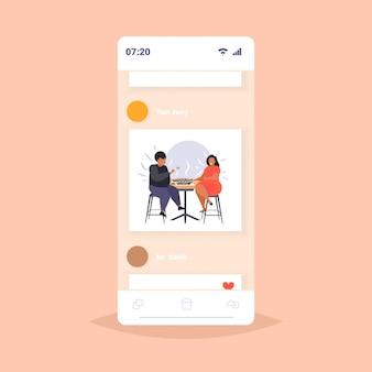 Fette fettleibige mannfrau, die sushi übergewichtiges afroamerikanisches paar isst, das am tisch sitzt, das zu mittag fettleibigkeit ungesundes ernährungskonzept smartphonebildschirm online mobile app isst