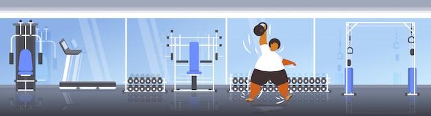 Fetter fettleibiger mann, der kettlebell übergewichtigen afroamerikaner hebt, der übungen trainiert, trainiert workout-gewichtsverlustkonzept modernes fitnessstudio-interieur