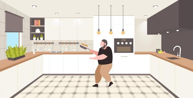 Fetter fettleibiger mann, der pfannkuchen in der bratpfanne ungesunde ernährung fettleibigkeit konzept übergewichtigen kerl bereitet frühstück moderne küche interieur