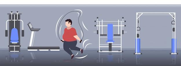 Fetter fettleibiger mann, der übungen mit springseil übergewichtigen kerl training workout gewichtsverlust konzept moderne turnhalle interieur in voller länge horizontal macht
