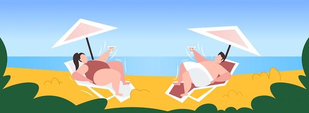 Fetter fettleibiger mann frau, die übergewichtiges paar sonnen, das cocktail trinkt, der auf sonnenliege unter regenschirm ungesunden lebensstil-fettleibigkeitskonzept am meer liegt