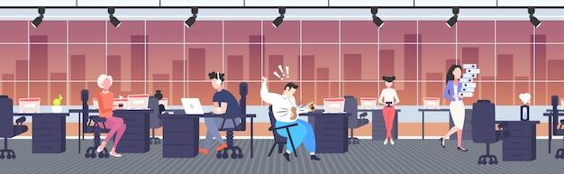 Fetter geschäftsmann, der kaffee auf übergewichtigem mann des hemdes mit fleck auf seinen kleidern verschüttet, die auf dem modernen büroinnenraumkonzept des fettleibigkeitskonzepts des stuhls sitzen