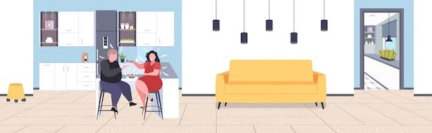 Fettleibiges paar, das süße leckere kuchen übergewichtige frau isst, die ihren fetten freund mit löffel ungesunder ernährung fettleibigkeitskonzept modernes wohnzimmer interieur füttert