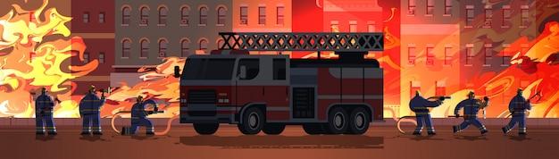 Feuerwehrmänner in der nähe von feuerwehrauto, die bereit sind, feuerlöscher in uniform und helmfeuerwehrnotfallkonzept zu löschen, das gebäudeaußenorangenflammenhintergrund horizontal brennt