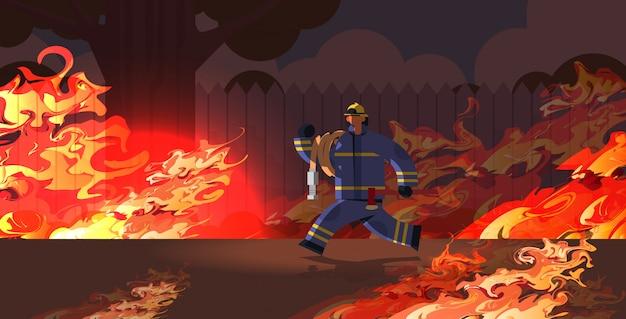Feuerwehrmann, der schlauchlöschflamme im brennenden haushinterhoffeuerwehrmann trägt, der uniform und helmfeuerwehrnotfallkonzept orange flamme trägt