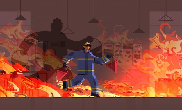 Feuerwehrmann mit feuerwehrmann mit roten eimern im einheitlichen feuerwehr-notdienst, der das feuerkonzept löscht, das die innere orange flamme des bürogebäudes brennt