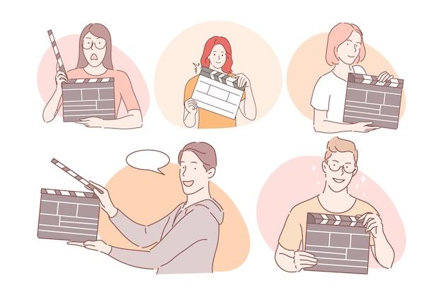 Filmemacher mit clapperboard-konzept. junge positive männer und frauen, die in der kinoproduktion mit filmklappe arbeiten und während des filmemachens für eine andere einstellung klatschen