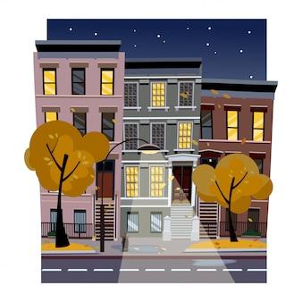 Flache karikaturvektorillustration der regnerischen stadtstraße des herbstes nachts. unebene häuser mit leuchtenden fenstern