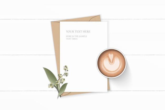 Flache lage draufsicht elegante weiße zusammensetzung brief kraftpapier umschlag blumenblatt und kaffee auf holzhintergrund.