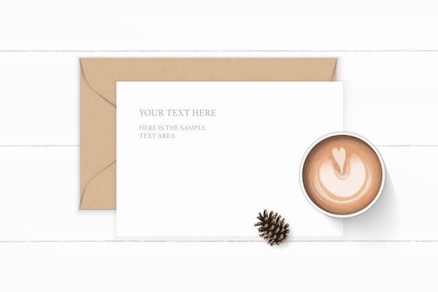 Flache lage draufsicht elegante weiße zusammensetzung brief kraftpapier umschlag tannenzapfen und kaffee auf holz hintergrund.