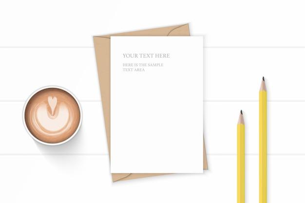 Flache lage draufsicht elegante weiße zusammensetzung brief kraftpapierumschlag gelbe stifte und kaffee auf holzhintergrund.