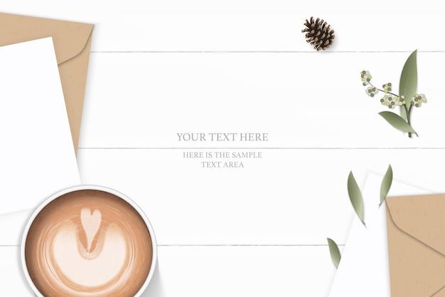 Flache lage draufsicht elegante weiße zusammensetzung brief kraftpapierumschlag tannenzapfenblatt blume und kaffee auf holzhintergrund.