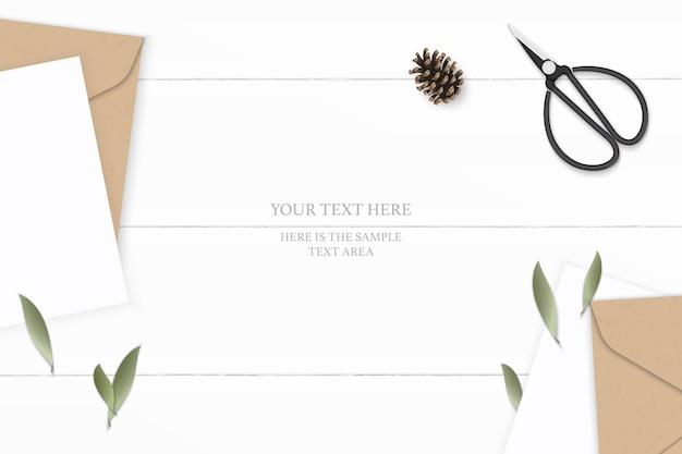 Flache lage draufsicht elegante weiße zusammensetzung brief kraftpapierumschlag tannenzapfenblatt und vintage metallschere auf holzhintergrund.