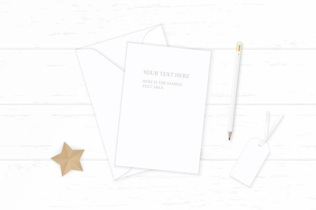 Flache lage draufsicht elegante weiße zusammensetzung briefpapier umschlag bleistift tag sternform handwerk auf holz hintergrund.