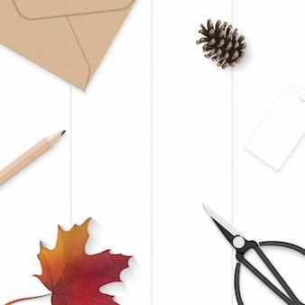 Flache lage draufsicht elegante weiße zusammensetzung papierblatt blume tannenzapfen kraft umschlag tag herbst ahornblatt und metallschere auf holzhintergrund.