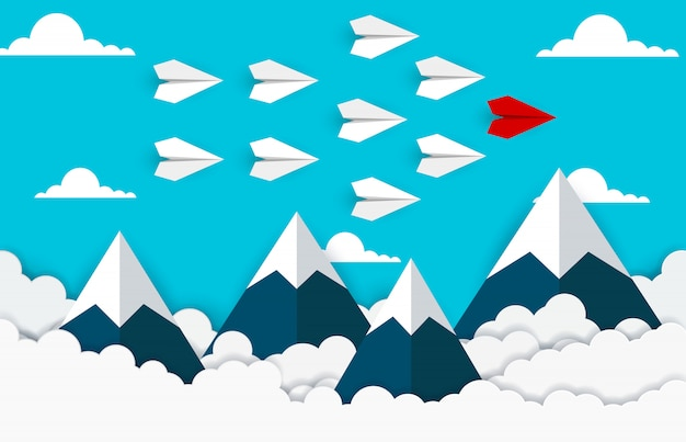 Flache rote und weiße papierfliege auf dem himmel zwischen wolke und berg