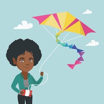 Fliegender drachen der jungen afroamerikanerfrau.